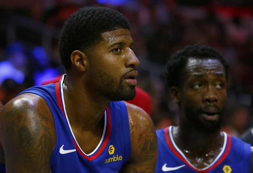 Clippers teammates Paul George, left, and Patrick Beverley watch a game from the sideline earlier this season.