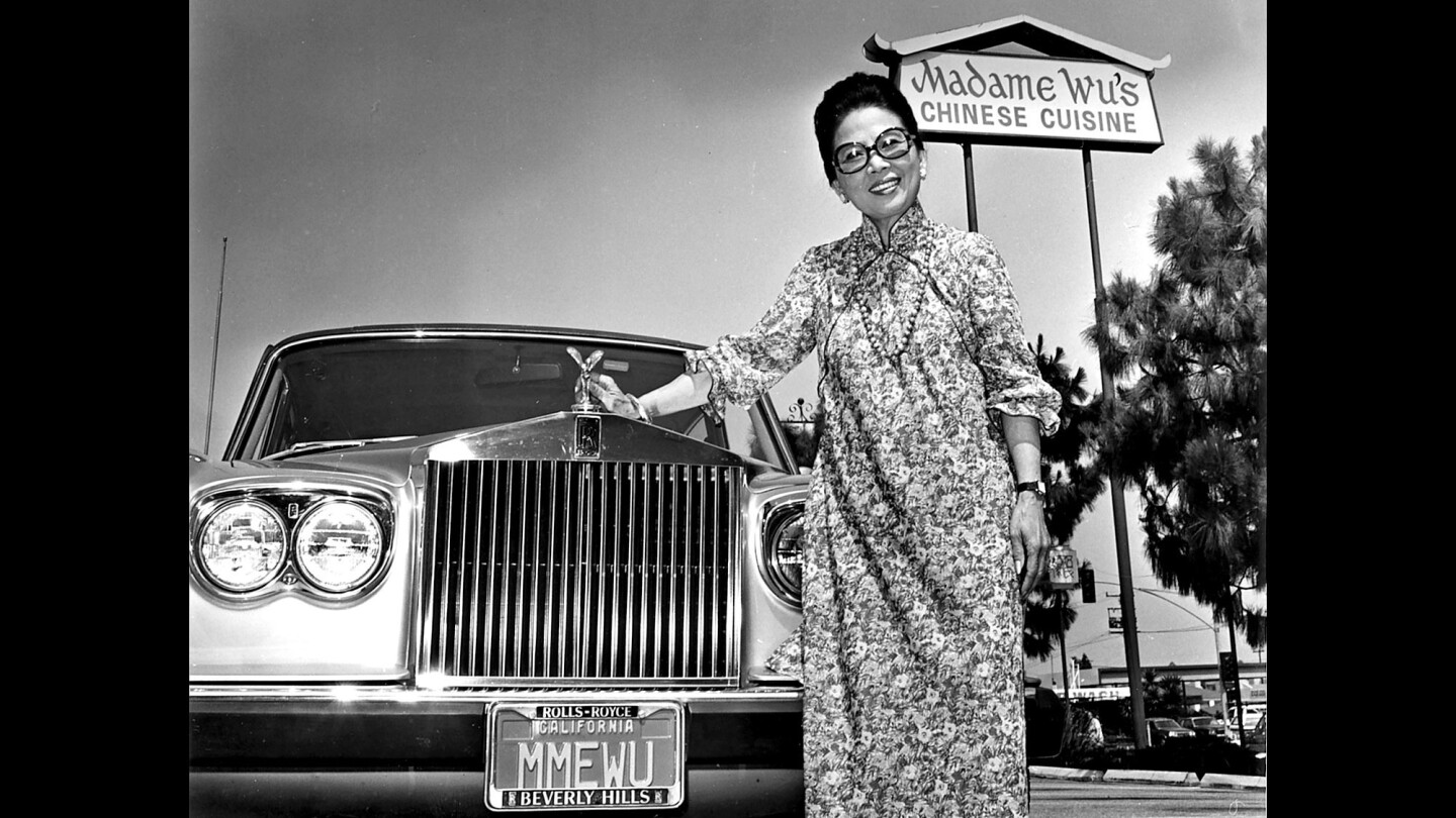 Madame Wu outside her restaurant with her Silver Cloud Rolls-Royce, which bore the license plate MMEWU.