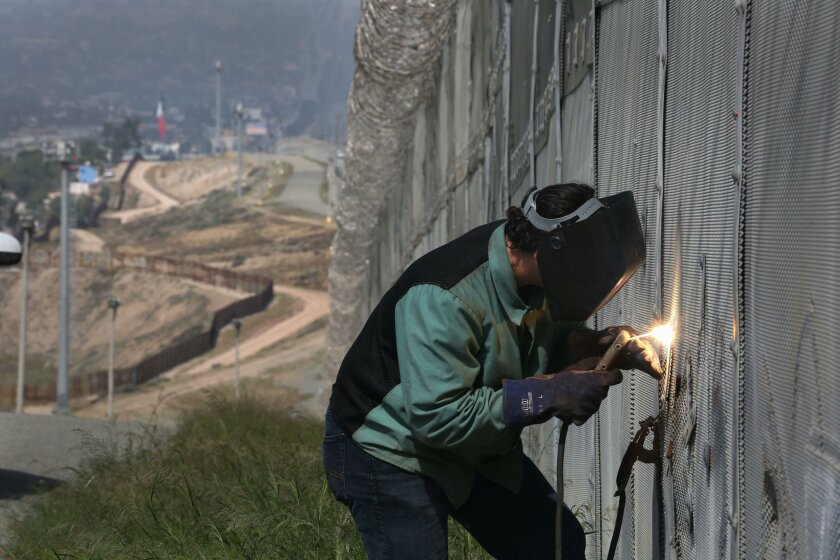 Border Patrol agent N.R. MacCallum welds a cut in the border fence Thursday north of the area in Tijuana known as Colonia Libertad.