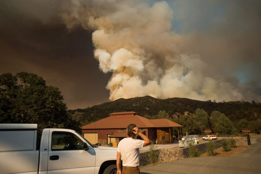 Plumes of smoke rise from the Rocky fire after it jumped Highway 20 near Clearlake Oaks, Calif., on Aug. 3.