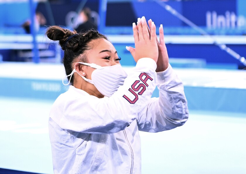 Olympic gold medalist Sunisa Lee claps in a white Team USA exercise suit