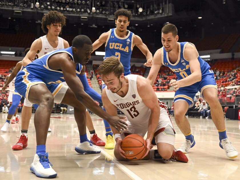 Washington State forward Jeff Pollard grabs a loose ball in front of UCLA's (from left) Prince Ali, Jules Bernard and Alex Olesinski.