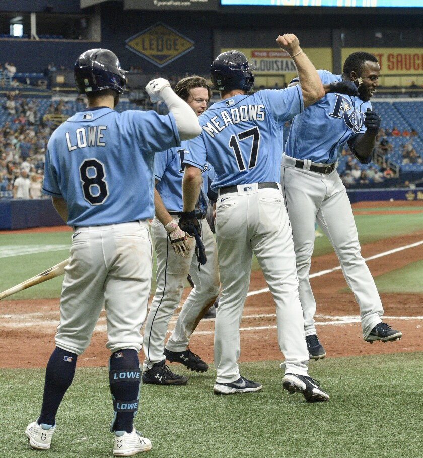 El bateador designado de los Rays de Tampa Bay, Randy Arozarena (derecha), celebra luego de pegar un grand slam durante la séptima entrada del juego de las Grandes Ligas contra los Orioles de Baltimore, el domingo 13 de junio de 2021, en San Petersburg, Florida. (AP Foto/Steve Nesius)