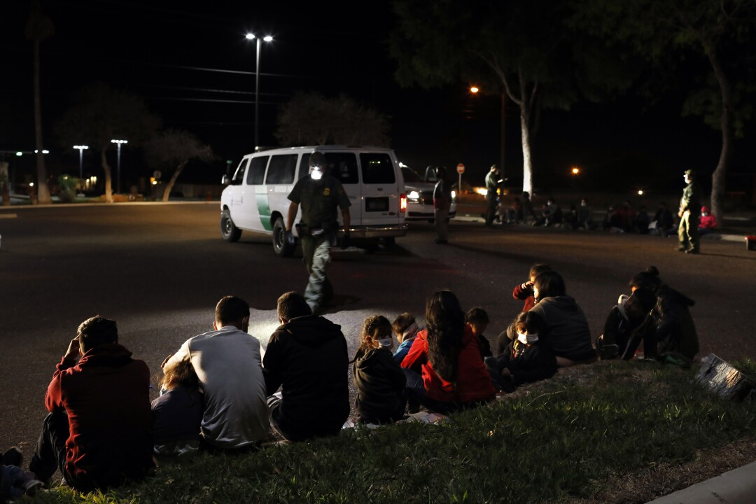 Families sit on a curb, waiting to be processed by Border Patrol