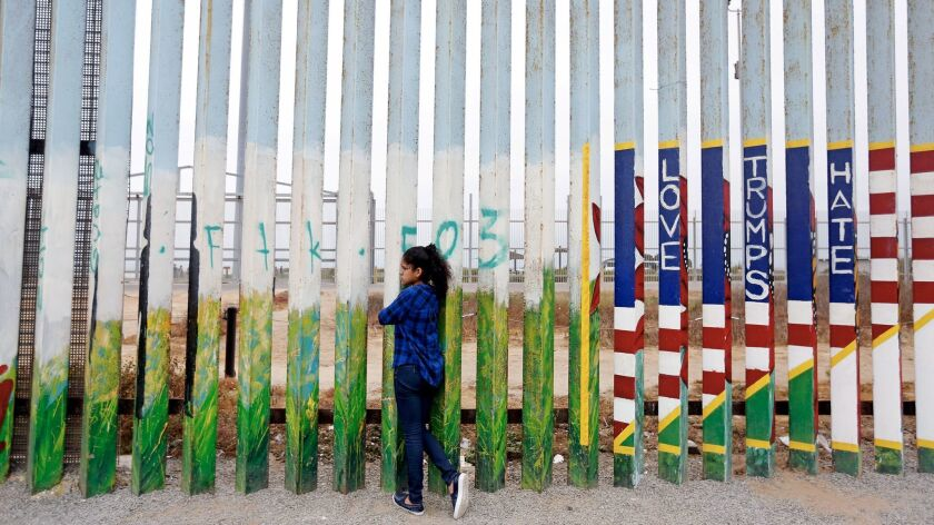 Jade Vega, 14, of Peru peers through the fence at Friendship Park at the beach along the U.S.-Mexico