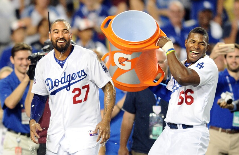 LOS ANGELES, CALIFORNIA OCTOBER 4, 2014-Dodgers Yasiel Puig, right, douses Matt Kemp with water afte