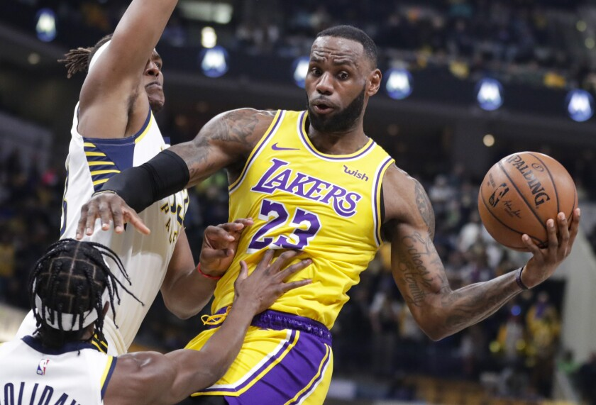 Lakers forward LeBron James passes in front of Indiana Pacers guard Aaron Holiday and center Myles Turner.