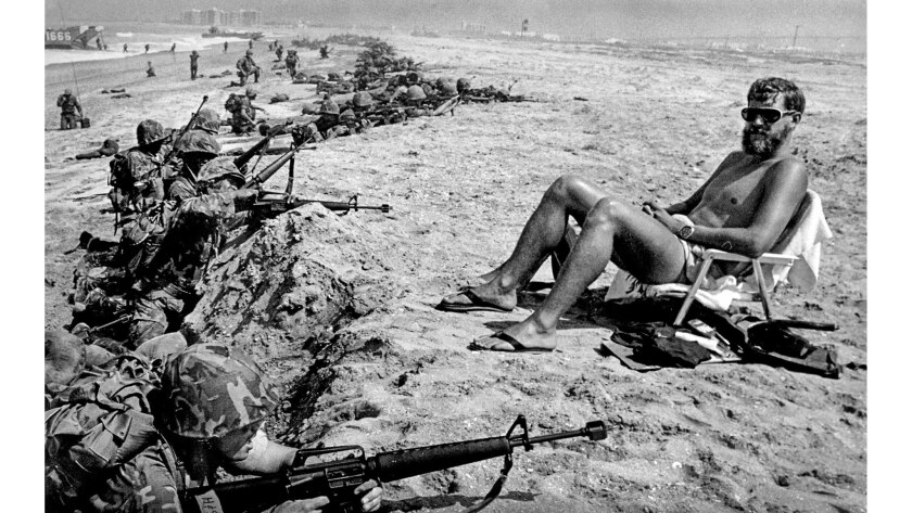 June 22, 1978: Marine Reservists during a training amphibious landing at Coronado capture one spectator — a Navy specialist getting some rays after planting dummy explosives.