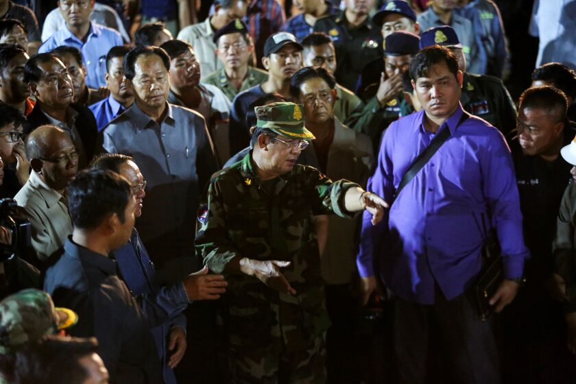Cambodia's Prime Minister Hun Sen (C in uniform) visits the site of an under-construction building two days after it collapsed in Sihanoukville early on June 24, 2019. - Victims of a Cambodia building collapse were buried alive as they slept, a survivor said on June 23, as the death toll at the Chinese-owned site rose to 18 and hopes faded for finding more survivors.