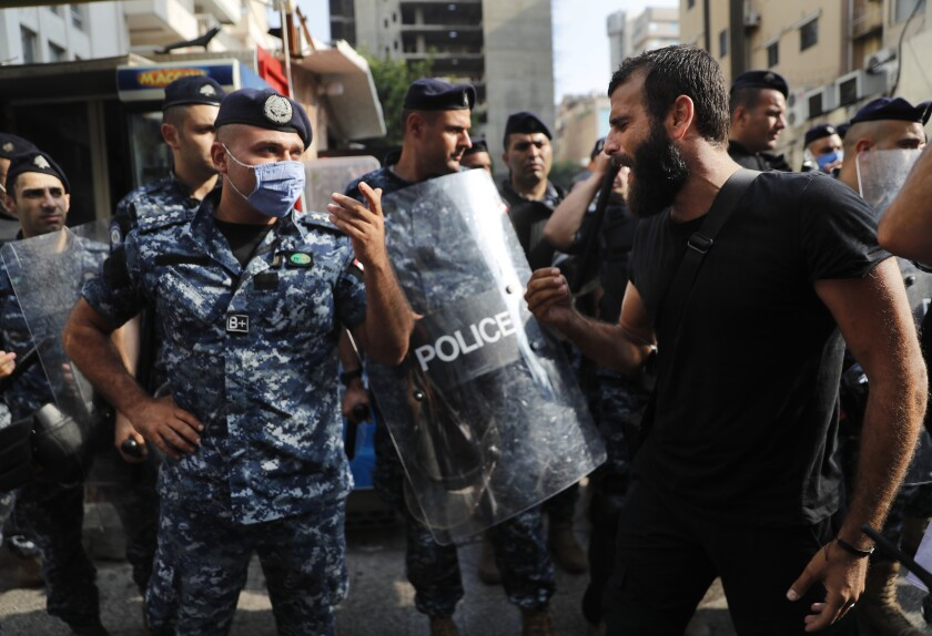 """An anti-government protester shouts at riot police, near the scene where a Lebanese man killed himself on Beirut's commercial Hamra Street, apparently because of the deteriorating economic and financial crisis in the country, in Beirut, Lebanon, Friday, July 3, 2020. The man left a note that reads in Arabic: """"I am not heretic but hunger is heresy,"""" words taken from a Lebanese song. Security officials said they were investigating the incident and motives for his suicide. (AP Photo/Hussein Malla)"""