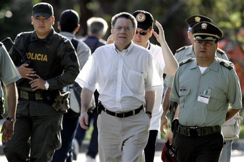 FILE - This Feb. 3, 2009 file photo, shows Colombia's former Peace Commissioner Luis Carlos Restrepo, center, arriving for a press conference in Villavicencio, Colombia. Colombia's Attorney office asked a judge in Bogota to issue an arrest warrant against Colombia's former Peace Commissioner Luis Carlos Restrepo, who faces charges on the alleged false demobilization of some rebels of Colombia's Revolutionary Armed Forces, FARC.(AP Photo/Fernando Vergara, file)
