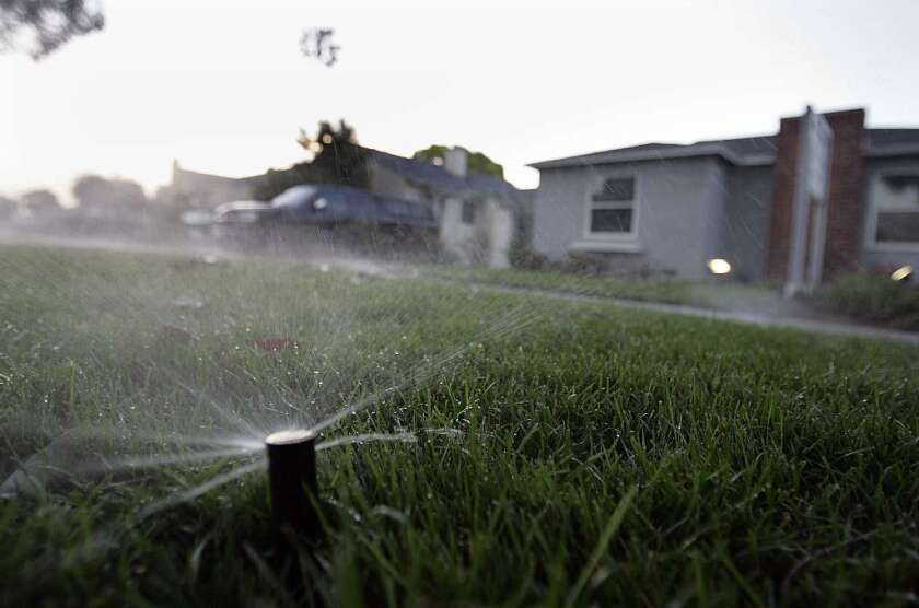 A running sprinkler is seen watering a lawn in Santa Monica. Research shows that reducing water use also has significant energy conservation benefits.