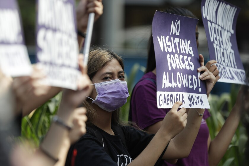 FILE - In this March 6, 2020, file photo, a woman protester wearing a protective mask holds a slogan during a rally outside the U.S. Embassy in Manila, Philippines against the planned military exercises between the Philippines and US under the Visiting Forces Agreement. The Philippines has decided not to suspend a defense pact with the U.S., avoiding a major blow to one of America's oldest alliances in Asia.(AP Photo/Aaron Favila, File)