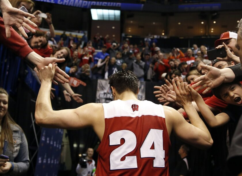 Wisconsin's Bronson Koenig is congratulated by fans as he leaves the court after hitting a three-point basket at the buzzer to defeat Xavier in a second-round men's college basketball game in the NCAA Tournament, Sunday, March 20, 2016, in St. Louis. Wisconsin won 66-63. (AP Photo/Jeff Roberson)