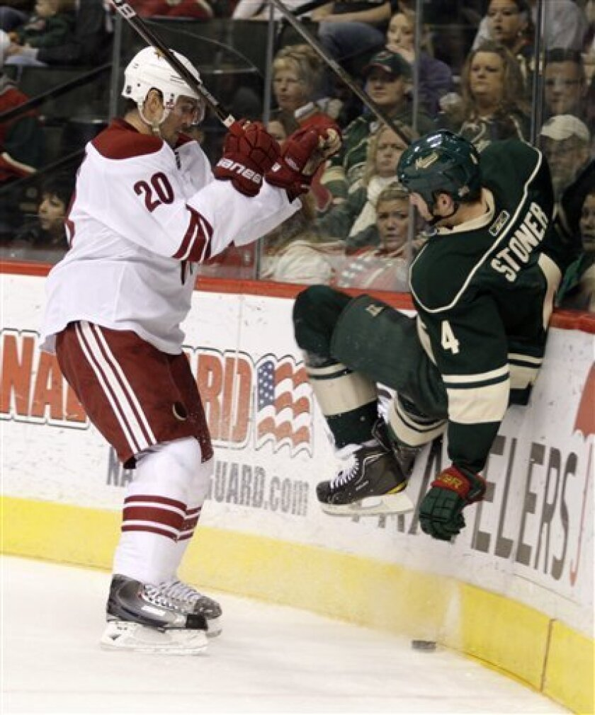 Minnesota Wild defenseman Clayton Stoner (4) is checked off the puck by Phoenix Coyotes center Eric Belanger (20) during the second period of an NHL hockey game, Sunday, Jan. 2, 2011, in St. Paul, Minn. (AP Photo/Paul Battaglia)
