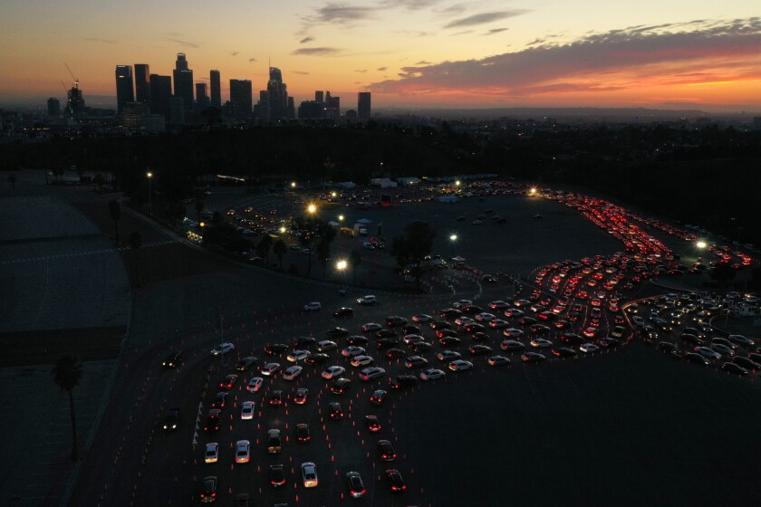 Snaking lines of car taillights six lanes wide at dusk, with the downtown L.A. skyline in the background
