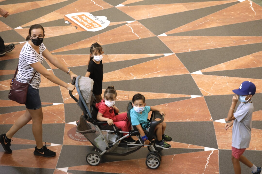 A woman pushes a double stroller with children. All wear masks.