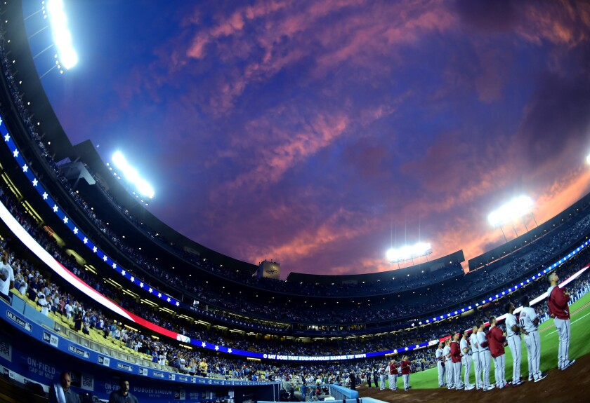 Players line up for the national anthem before a game at Dodger Stadium.