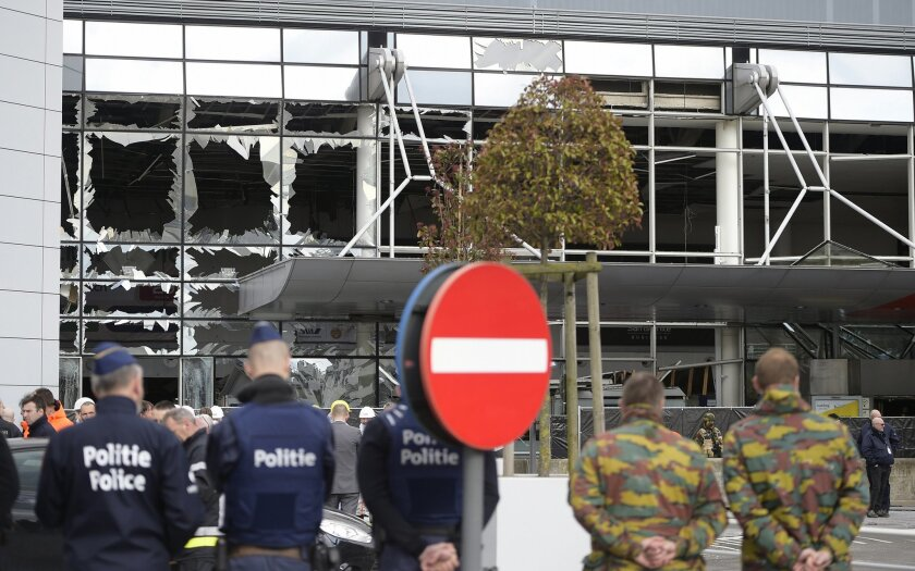 Police and soldiers from the Belgian Army stand in front of blown out windows at Zaventem Airport in Brussels on Wednesday, March 23, 2016. Belgian authorities were searching Wednesday for a top suspect in the country's deadliest attacks in decades, as the European Union's capital awoke under guard and with limited public transport after scores were killed and injured in bombings on the Brussels airport and a subway station. (AP Photo/Yorick Jansens, Pool photo via AP)