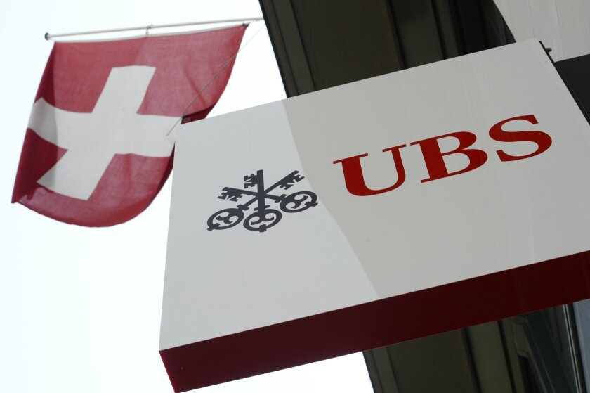 """FILE - The April 24, 2014 file photo shows the logo of Swiss bank UBS and the Swiss flag in Zurich, Switzerland.  UBS has reported a 71 percent increase in third quarter profit, Tuesday Nov. 3, 2015, as the banking giant took a big tax benefit, while predicting """"substantial"""" future costs from new S"""