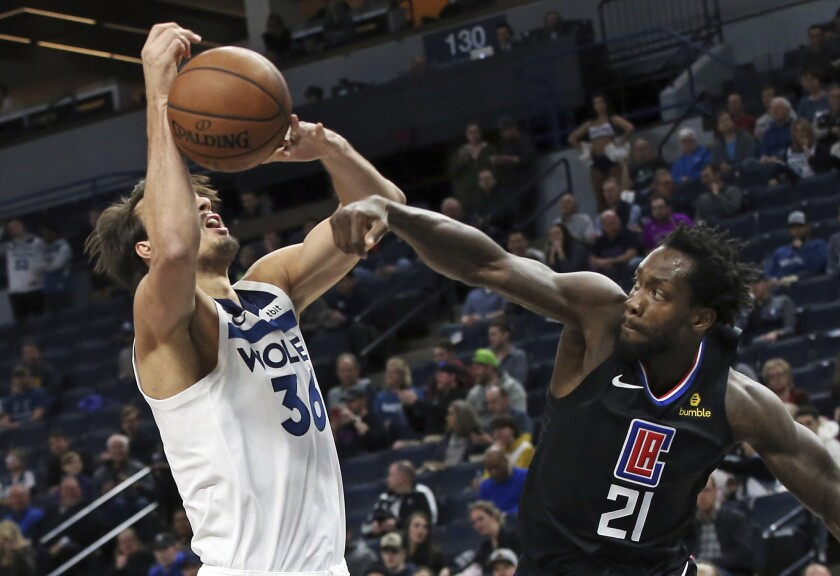 Clippers point guard Patrick Beverley knocks the ball from the grasp of Timberwolves forward Dario Saric during a game.