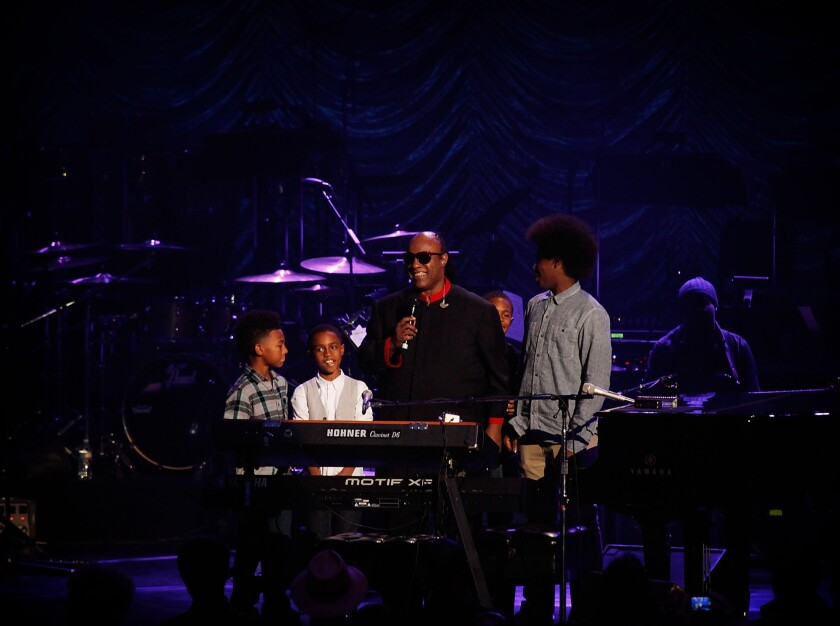 Stevie Wonder performs on stage with his grandchildren during his 18th annual House Full of Toys benefit concert.