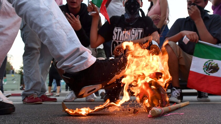 A Trump hat burns during a protest near where Republican presidential candidate Donald Trump held a rally in San Jose in June.