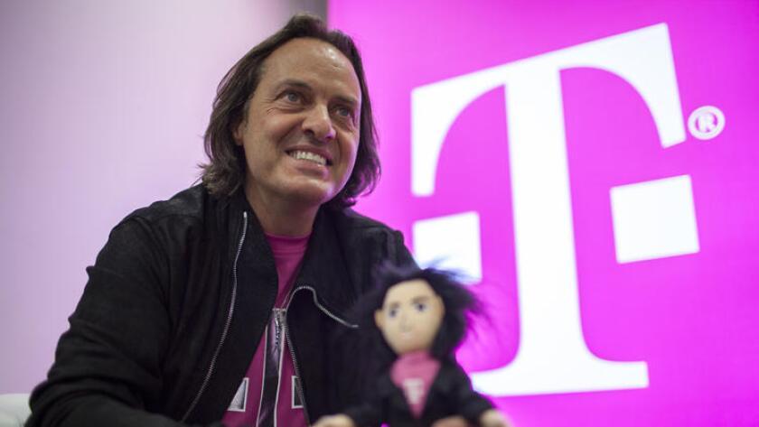John Legere, CEO de T-Mobile sostiene un muñeco a su imagen y semejanza durante un evento mediático en el año 2014.