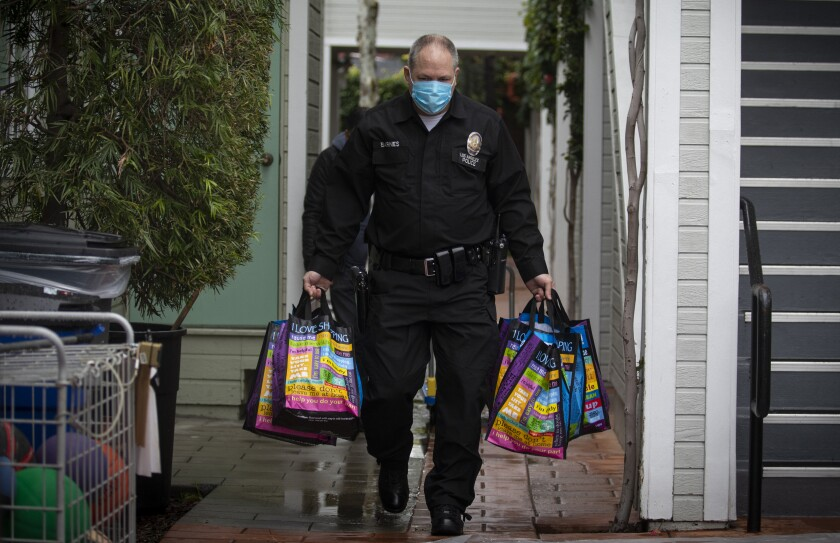 LAPD Officer Kirk Barnes carries bags of food on Thursday while making deliveries to Hollywood seniors.