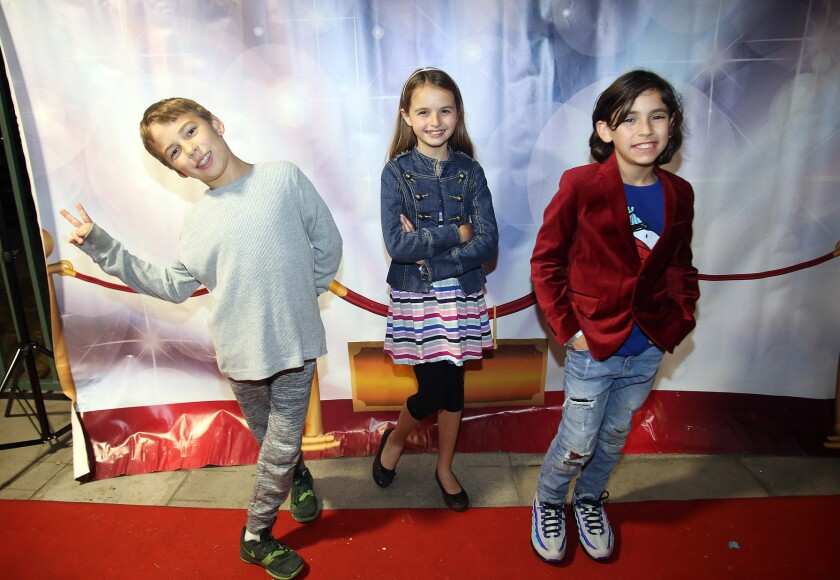 Grady Pullin, 9, left, Hannah Dufour, 9, and Jamison Karp, 9, all fourth-grade filmmakers from Stevenson Elementary School, pose for pictures on the red carpet before the premiere of the second annual Fourth Grade Film Festival at Stevenson on Wednesday.