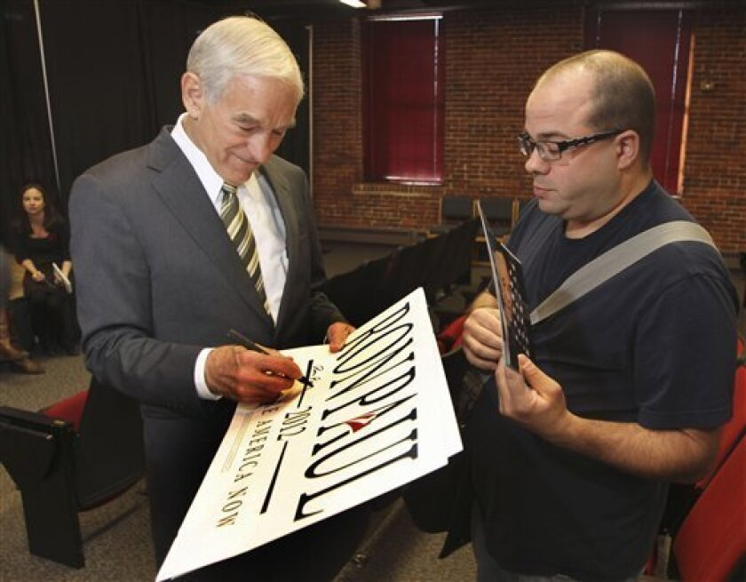 Republican presidential candidate, Rep. Ron Paul, R-Texas autographs a sign after speaking students at the University of New Hampshire's Manchester campus, Monday, Oct. 3, 2011, in Manchester, N.H. (AP Photo/Jim Cole)