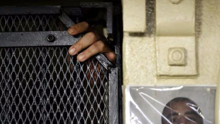 In this photo taken on Tuesday, Dec. 29, 2015, the fingers of Martin Navarette reach out of his cell on death row at San Quentin State Prison in San Quentin, Calif.