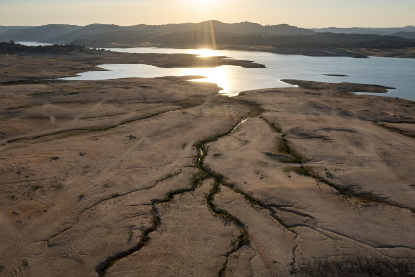 Dry, cracked mud surrounds a lake that gleams in the sun