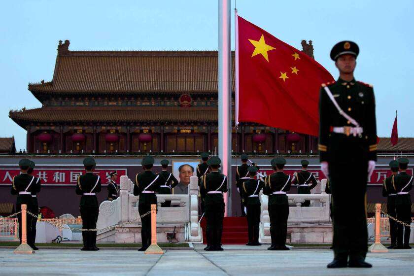 The Chinese flag is lowered in Tiananmen Square on the eve of the Communist Party congress, which will usher in the country's new leaders.