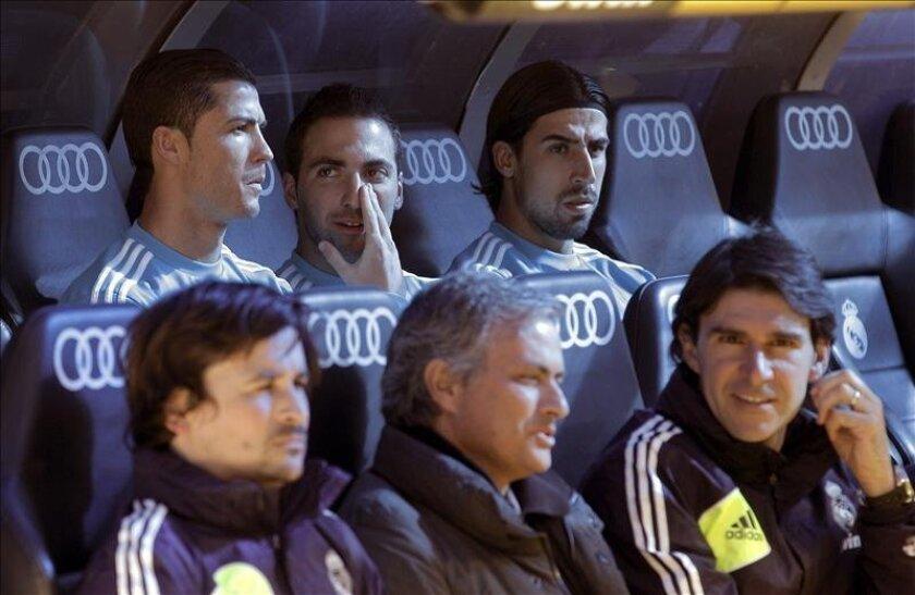 Los jugadores del Real Madrid Cristiano Ronaldo (i), Gonzalo Higuaín (c) y Sami Khedira, en el banquillo junto al entrenador, José Mourinho (primer término, c) y su ayudante, Aitor Karanka. EFE/Archivo