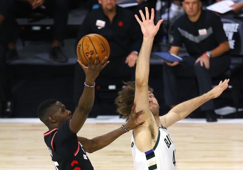 Toronto Raptors' Chris Boucher, left, shoots against Milwaukee Bucks' Robin Lopez, right, during the third quarter of an NBA basketball game Monday, Aug. 10, 2020, in Lake Buena Vista, Fla. (Mike Ehrmann/Pool Photo via AP)