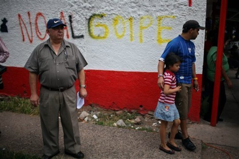 """People stand by graffiti that reads in Spanish """"No to the coup"""" on the sidelines of a protest by supporters of Honduras' ousted President Manuel Zelaya in Tegucigalpa, Saturday, Oct. 10, 2009.  Signs of progress have emerged from two days of talks and Honduras' rival factions plan to resume after a"""