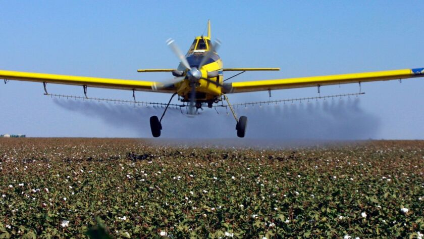 A plane releases pesticides in Lemoore, Calif., in 2001.