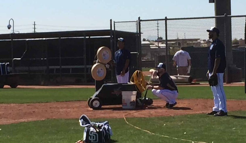Padres bench coach Dave Roberts uses the team's new FungoMan machine to hit a variety of fly balls to outfielders.