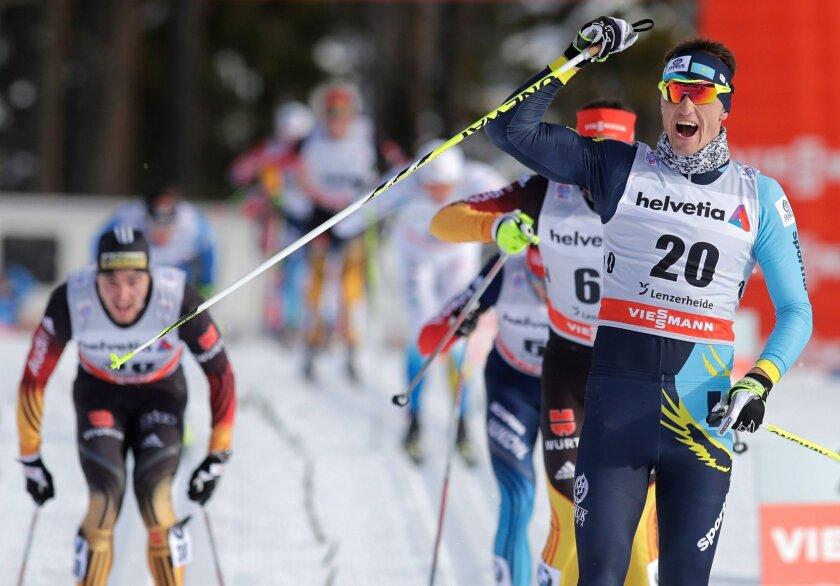 Alexey Poltoranin of Kazakhstan celebrates after winning the men's 15-kilometer Mass Start race at the cross country Tour de Ski competition in Lenzerheide, Switzerland, Wednesday, Jan. 1, 2014. (AP Photo/Keystone, Arno Balzarini)