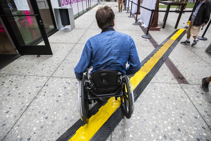 Radcliff navigates his wheelchair over an electric cable channel at the Bloc shopping complex.