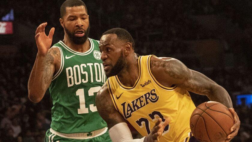Lakers' LeBron James dribbles past Boston Celtics' Marcus Morris at Staples Center on Saturday.