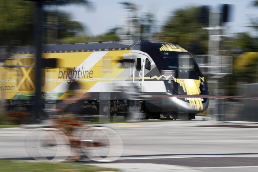 FILE - In this Wednesday, Nov. 27, 2019 file photo, a Brightline passenger train passes by in Oakland Park, Fla. On Tuesday, Aug. 10, 2021, the company said it will resume service sometime in November, 20 months after it closed because of the pandemic. (AP Photo/Brynn Anderson)