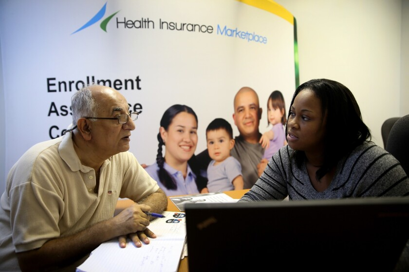 An Obamacare enrollment specialist helps a man sign up for health insurance through the Affordable Care Act in Miami in December.