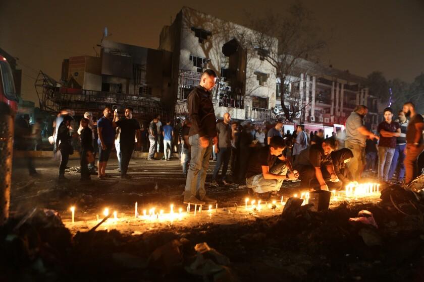 Residentes encienden velas en el lugar donde se registró un brutal ataque con auto bomba en Karada, un concurrido distrito comercial de la capital iraquí, Bagdad, donde las víctimas realizaban compras para el feriado Eid al-Fitr, el 3 de julio de 2016. (AP Foto/Hadi Mizban)