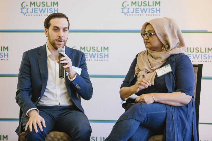 In this May 22, 2018 photo provided by the Muslim Jewish Advisory Council, writers Yair Rosenberg and Rabia Chaudry attend an interfaith Iftar in San Francisco.