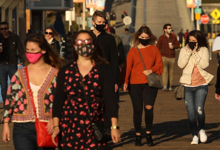 People, most wearing masks, walk on the Santa Monica Pier on Monday.