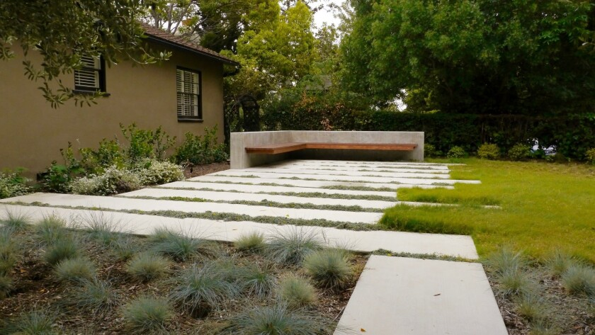 New hardscape and a built-in bench provide flexible space where the family can relax and engage with the neighborhood.