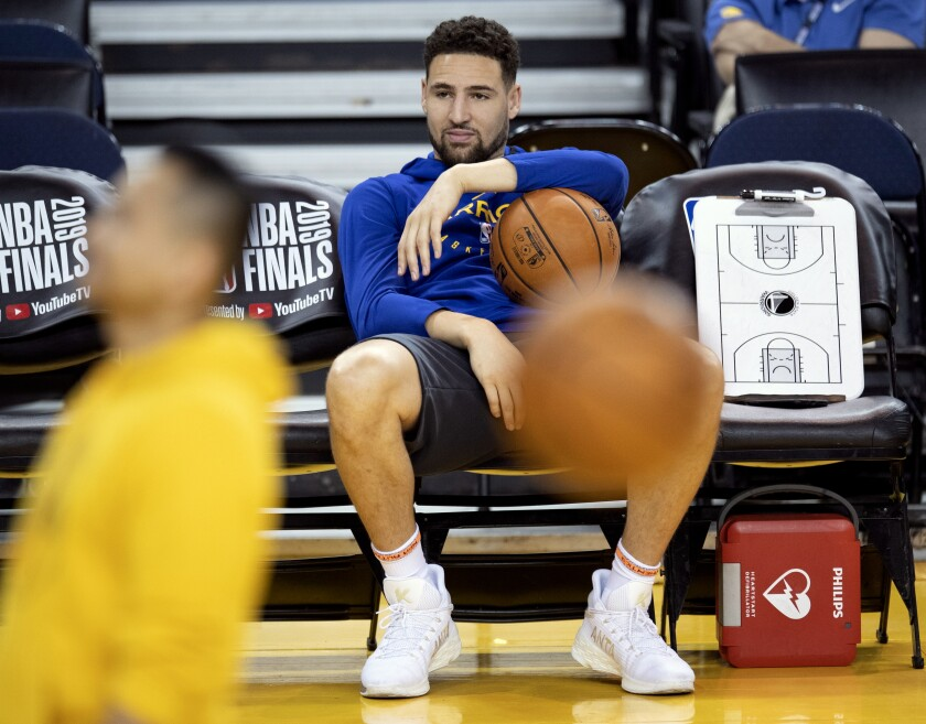 FILE- In this June 4, 2019, file photo, Golden State Warriors' Klay Thompson sits on the bench watching teammates during practice for the NBA Finals against the Toronto Raptors in Oakland, Calif. The Warriors said Thursday, Nov. 19, 2020, that Thompson has suffered a torn right Achilles tendon and is expected to miss the upcoming season. Thompson was injured during a pickup game in Southern California the day before. (Frank Gunn/The Canadian Press via AP, File)