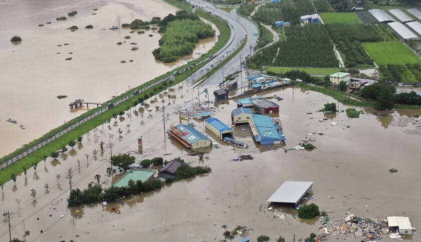 A village area is flooded near Seomjin River, left, due to heavy rain in Hadong, South Korea, Saturday, Aug. 8, 2020. (Kim Dong-min/Yonhap via AP)